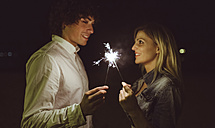 Young couple in love holding sparklers on the beach at night - DAPF000299