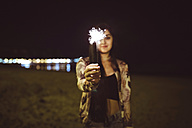 Young woman holding sparkler on the beach at night - DAPF000302