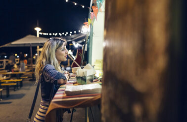 Young woman waiting in front of food stall at summer night festival - DAP000305