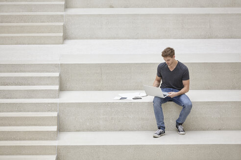 Young man sitting on stairs using laptop - FMKF002976