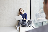 Smiling young woman sitting at concrete wall with laptop looking at man - FMKF003006
