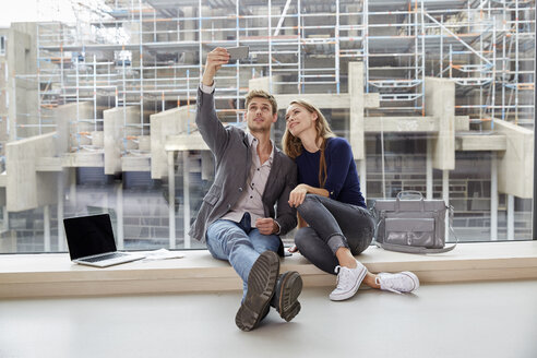 Young couple sitting at the window taking a selfie - FMKF003009