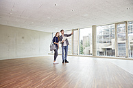 Young man and woman with documents talking in empty room - FMKF003012