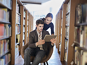 Young man and woman using tablet in library - FMKF003018