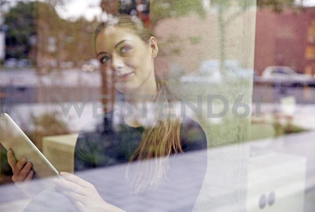 Young woman holding tablet looking out of window - FMKF003021