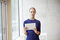 Portrait of young woman holding tablet - FMKF003024