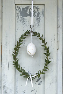 Easter egg and box tree wreath hanging in front of wooden door - ASF005995