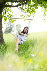 Woman taking selfie with tablet in a hanging chair under a tree - MAEF011949