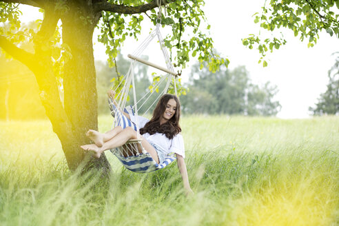 Happy woman relaxing in a hanging chair under a tree - MAEF011952