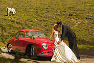 Groom kissing bride leaning on car bonnet of red vintage car - FC001067