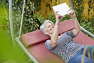 Woman relaxing on a swing in the garden using digital tablet - FMKF003027