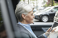 Portrait of businesswoman sitting in a car using tablet - FMKF003036