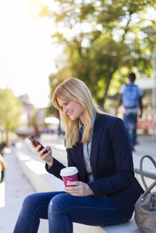 Smiling b businesswoman with coffee to go looking at smartphone - NAF000017
