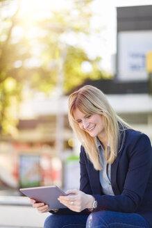 Smiling businesswoman using tablet - NAF000020