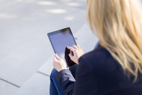 Hand of businesswoman touching display of tablet - NAF000023