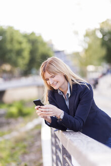 Smiling businesswoman leaning on railing looking at cell phone - NAF000029