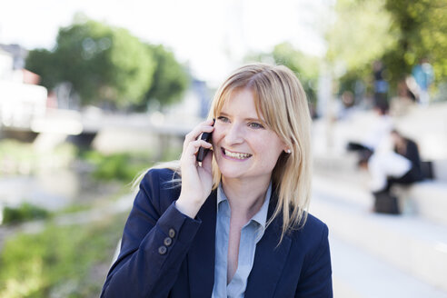 Portrait of smiling blond businesswoman on the phone - NAF000032