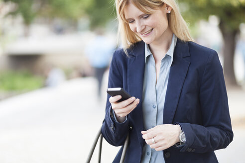 Smiling blond businesswoman looking at smartphone - NAF000035
