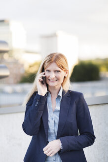 Portrait of smiling blond businesswoman on the phone - NAF000038