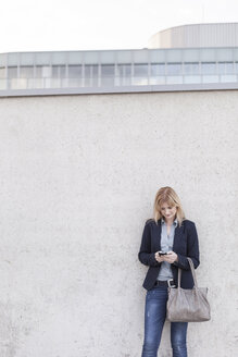 Blond businesswoman standing in front of wall looking at smartphone - NAF000041