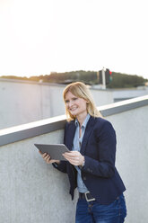Smiling businesswoman with tablet looking at distance - NAF000044
