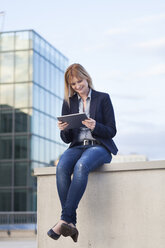 Smiling businesswoman sitting on a wall looking at tablet - NAF000050