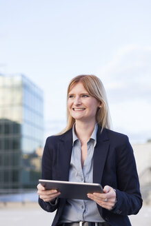 Portrait of smiling businesswoman with tablet - NAF000053
