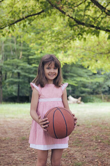 Smiling little girl with basketball wearing pink dress - XCF000103