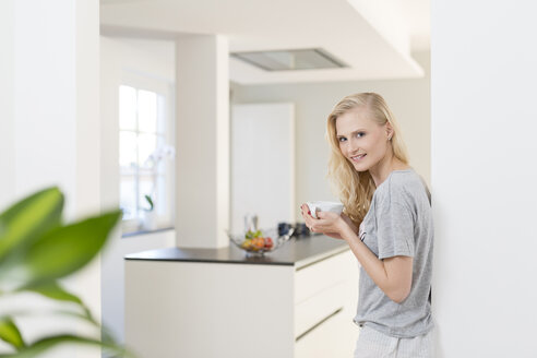 Smiling blond woman with cup of coffee in kitchen - SHKF000647
