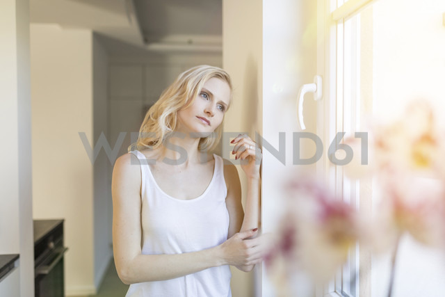 Blond woman at home looking out of window - SHKF000650