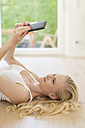 Blond woman lying on wooden floor reading e-book - SHKF000656