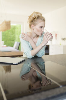 Woman in kitchen drinking glass of water - SHKF000659