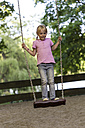 Little girl standing on a swing at playground - JFEF000803