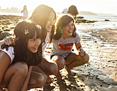 Three happy girls on the beach at sunset - MGOF002265