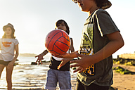 Kids playing with a ball on the beach at sunset - MGOF002283