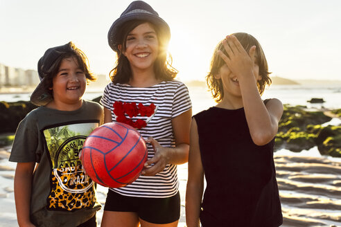 Three happy kids with ball on the beach at sunset - MGOF002292