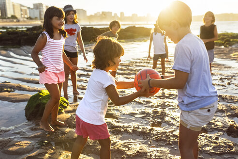 Kids playing with a ball on the beach at sunset - MGOF002301