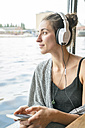 Relaxed woman listening music with headphones - TAMF000567