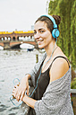 Germany, Berlin, relaxed woman listening music with headphones - TAMF000573