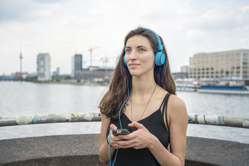 Germany, Berlin, relaxed woman listening music with headphones - TAMF000576