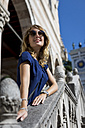 Italy, Udine, portrait of happy blond tourist wearing sunglasses - MAUF000836