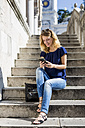 Italy, Udine, smiling blond woman sitting on stairs looking at cell phone - MAUF000839