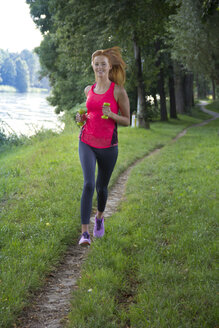 Young woman jogging with dumbbells - YFF000565
