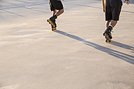 Legs of men with rollerblades skating - ABZF001028