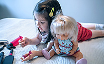 Girl playing with doll and hairdressing toys - DAPF000313