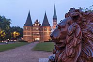 Germany, Luebeck, lion statue in front of the town gate Holstentor and Church of St. Peter at dusk - PCF000262