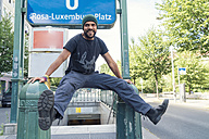 Young single in Berlin-Mitte, in front of underground sign Rosa-Luxemburg-Platz - TAMF000590
