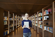 Portrait of young woman holding tablet in library - FMKF003041