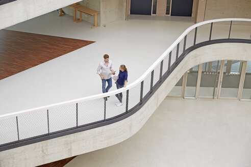 Young man and woman talking in modern office building - FMKF003053