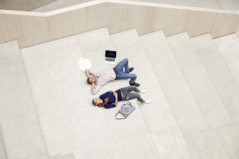 Young man and woman lying on staircase in a building - FMKF003056